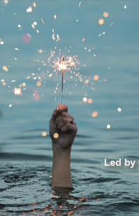 A hand holding a sparkler coming out of the deep water.